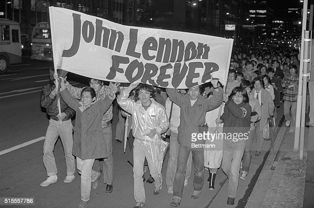 About five thousand Japanese fans of John Lennon carry a banner which says John Lennon Forever as they march through the streets of the Ginza...