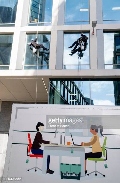 Above an illustration of two women office workers at their desks who appear on the side of parked van, two male contractors abseil down to clean the...