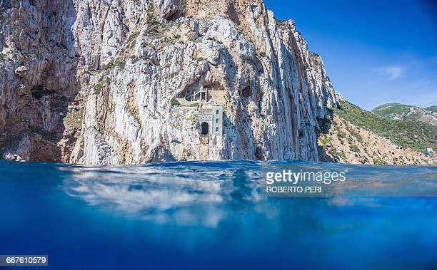 Above and below view of blue sea and cliffs, Masua, Italy
