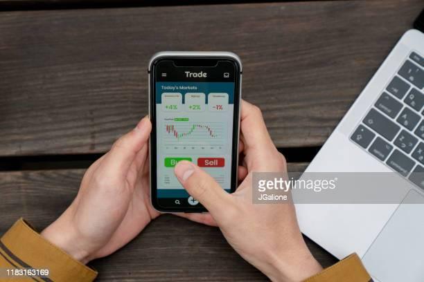 oberwinkelansicht eines jungen mannes mit einer trading-app - börsenhandel finanzberuf stock-fotos und bilder