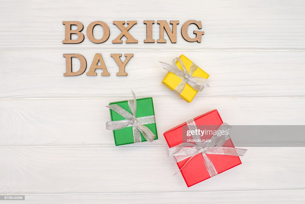 above gift boxes is tied with a ribbon with words boxing day on wood