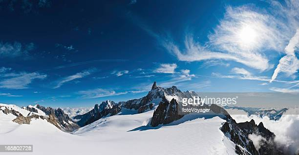 Above the clouds snow summit sunburst panorama Alps Italy