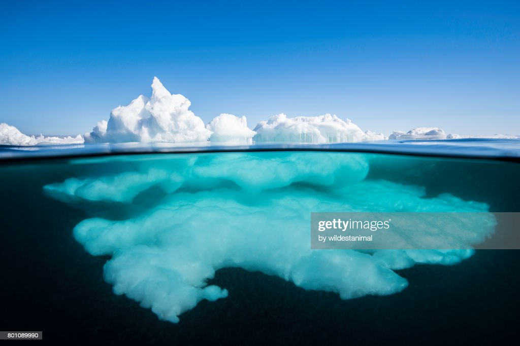 Above the surface and below the surface view of ice formations at the ice floe edge on a bright sunny day, northern Baffin Island, Canada. : Foto de stock