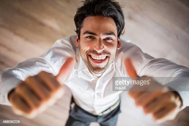 Vista de arriba de hombre de negocios feliz mostrando pulgar hacia arriba.
