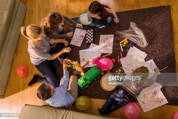 above view of a woman playing with small kids on carpet at home. - drawing activity stock pictures, royalty-free photos & images