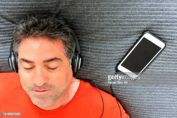 above view of adult man listening to music on bed - rafael ben ari fotografías e imágenes de stock