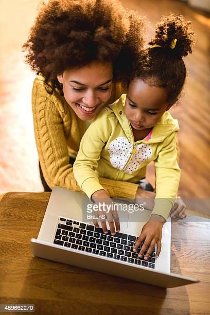 Vue plongeante de afro-américain mère et fille à l'aide d'un ordinateur portable.