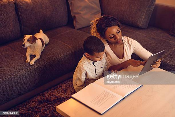 above view of african american mother and son at home. - elektronische organiser stockfoto's en -beelden
