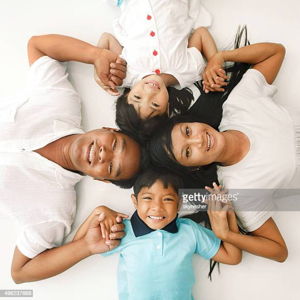 Above view of Asian family lying on the floor.