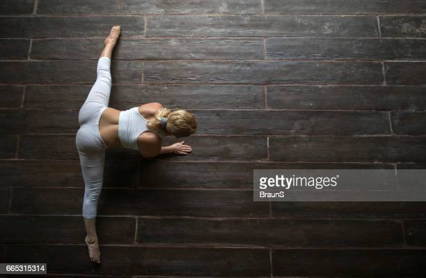 above view of athletic woman doing relaxation exercises on floor. - doing the splits stock pictures, royalty-free photos & images