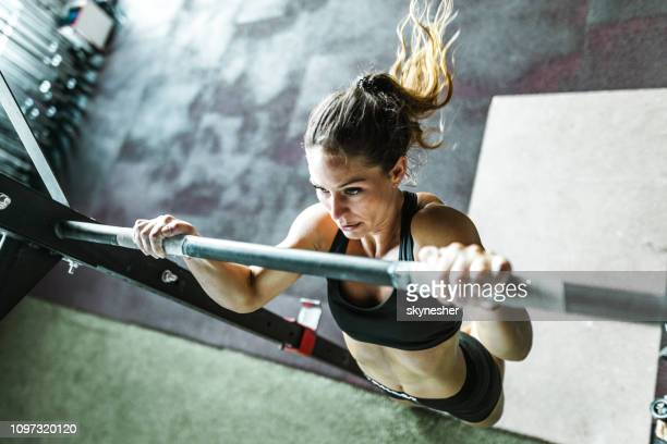 above view of athletic woman exercising chin-ups in a gym. - chin ups stock photos and pictures