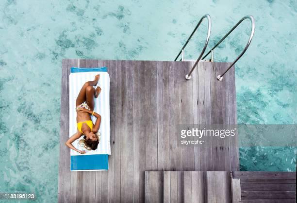 au-dessus de la vue de la belle femme prenant un bain de soleil sur la chaise de pont à une jetée. - femme maillot de bain photos et images de collection