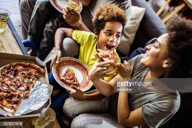 above view of black mother feeding her daughter with pizza at home. - take away food stock pictures, royalty-free photos & images