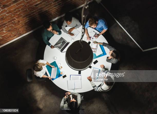 above view of business colleagues analyzing reports on a meeting at the table. - circle stock pictures, royalty-free photos & images
