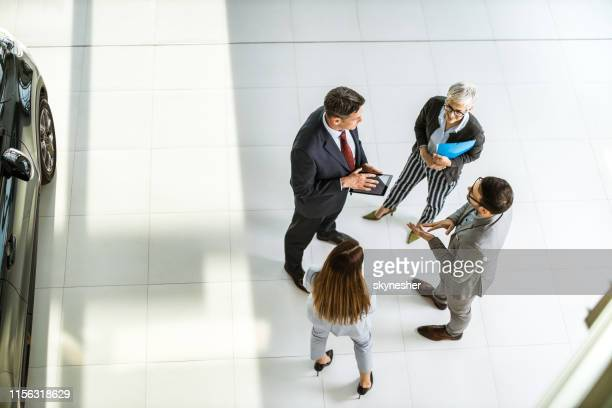 above view of business team talking to car salesperson in a showroom. - showroom stock pictures, royalty-free photos & images