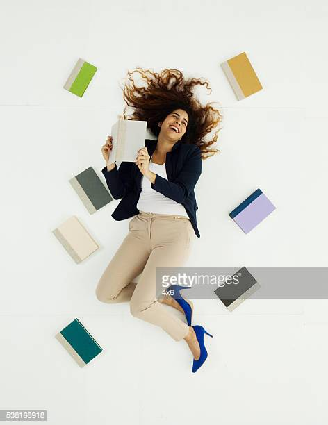 Above view of businesswoman lying with books