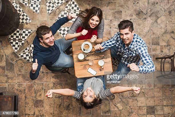 Vista superior de alegres amigos no café e olhando para a câmara.