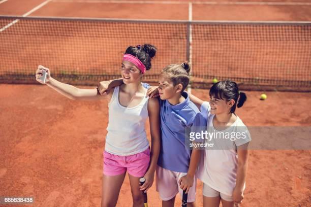 Above view of children taking selfie on tennis court.