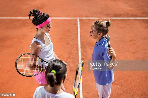 Above view of children tennis players talking on tennis court.