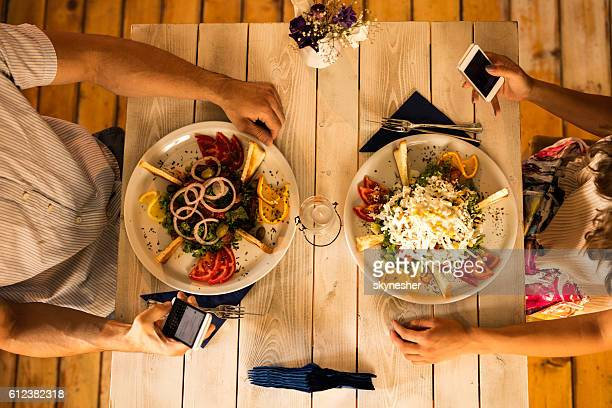 Above view of couple using cell phones at dining table.