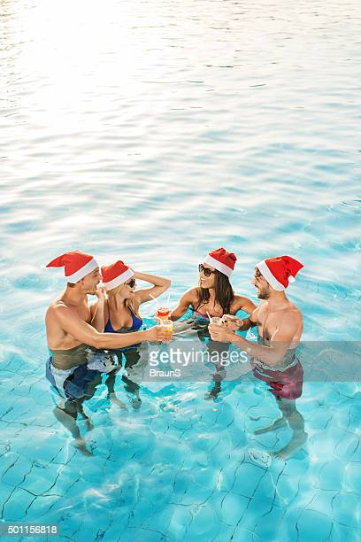 Above view of couples celebrating Christmas in the swimming pool.