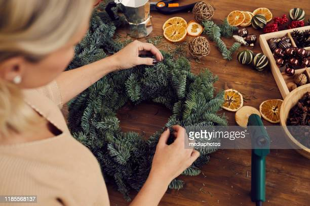 above view of craftswoman standing at wooden table full of decorations and creating christmas wreath in workshop - wreath stock pictures, royalty-free photos & images