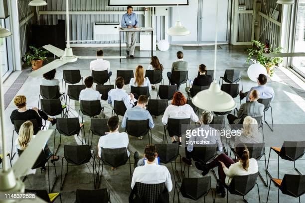 above view of crowd of entrepreneurs having training class in a board room. - seminar stock pictures, royalty-free photos & images