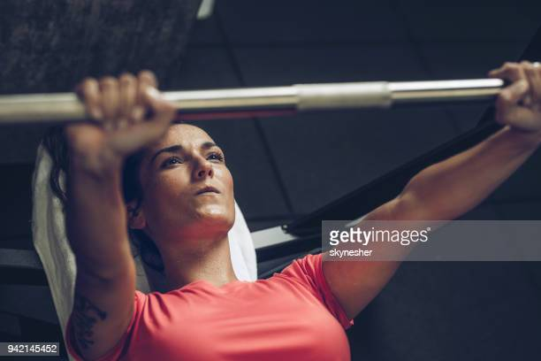 Above view of determined sportswoman exercising bench press in a gym.
