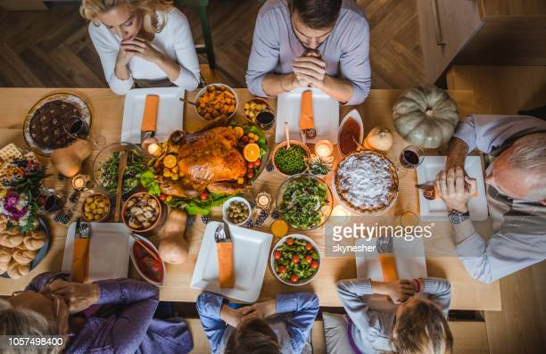above view of extended family saying grace before thanksgiving dinner. - religious christmas stock photos and pictures