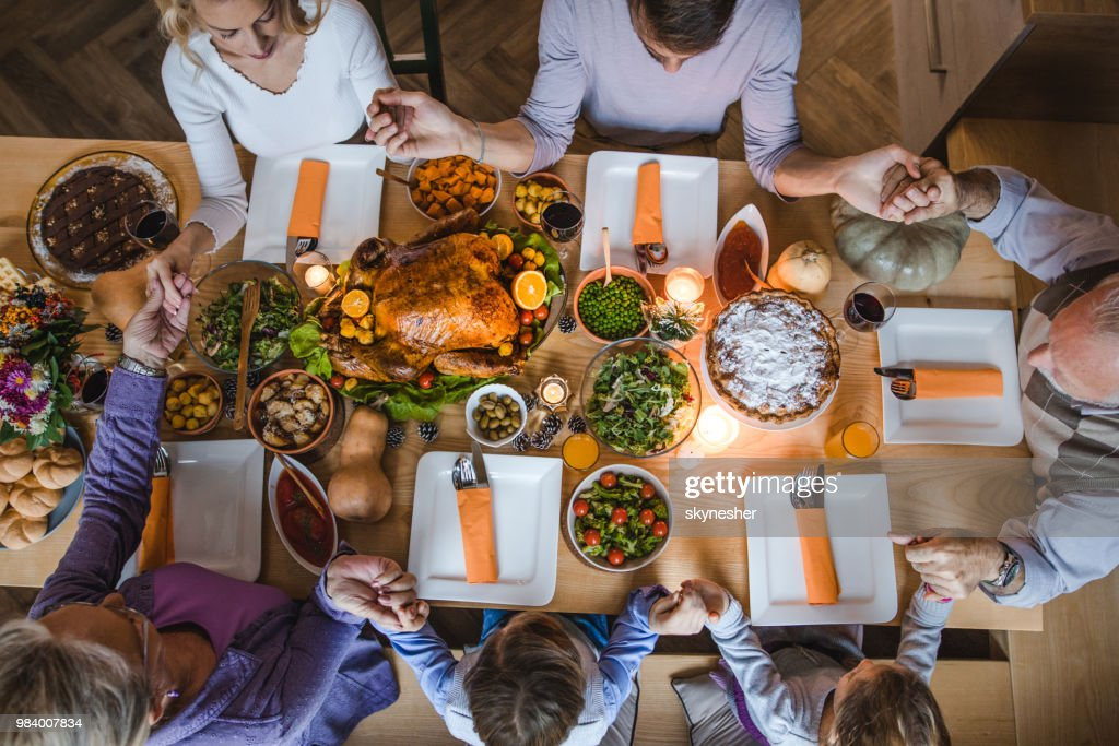Above view of extended family saying grace before Thanksgiving dinner. : Stock Photo