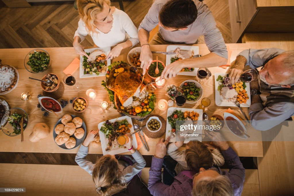 Above view of extended family talking at Thanksgiving dinner. : Stock Photo