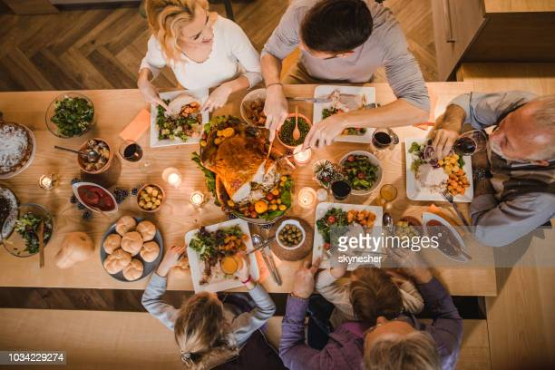 above view of extended family talking at thanksgiving dinner. - evening meal stock pictures, royalty-free photos & images