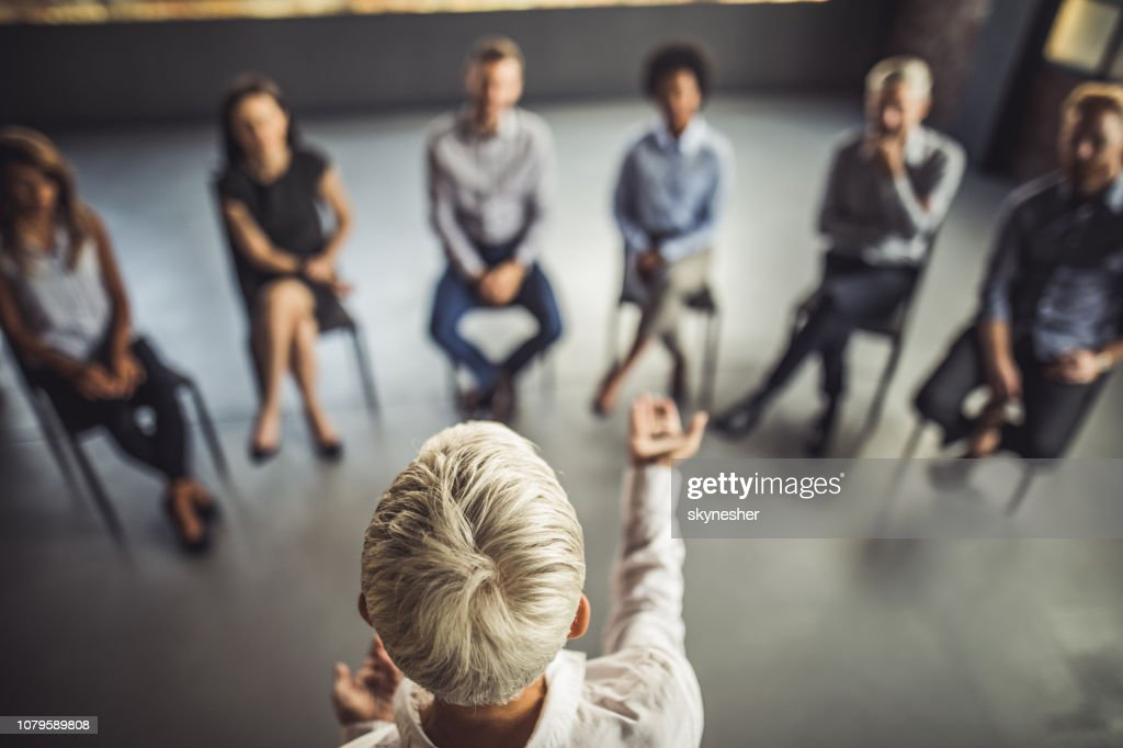Above view of female instructor leading a business group therapy. : Stock Photo