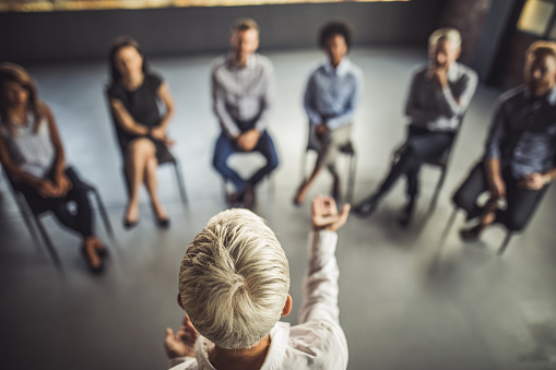 Above view of female instructor leading a business group therapy. 1079589808