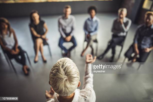 above view of female instructor leading a business group therapy. - leadership stock pictures, royalty-free photos & images