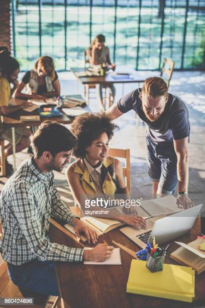 above view of freelance workers using laptop while working at casual office. - university student stock pictures, royalty-free photos & images