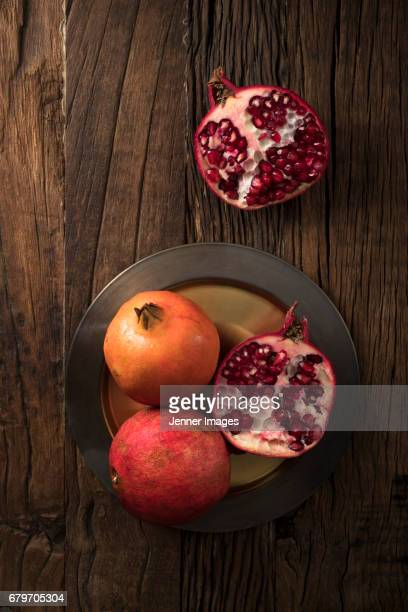 Above View Of Fresh Pomegranates On Rustic Wooden Table.