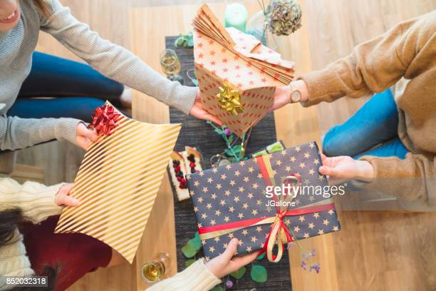 Above view of friends exchanging Christmas presents