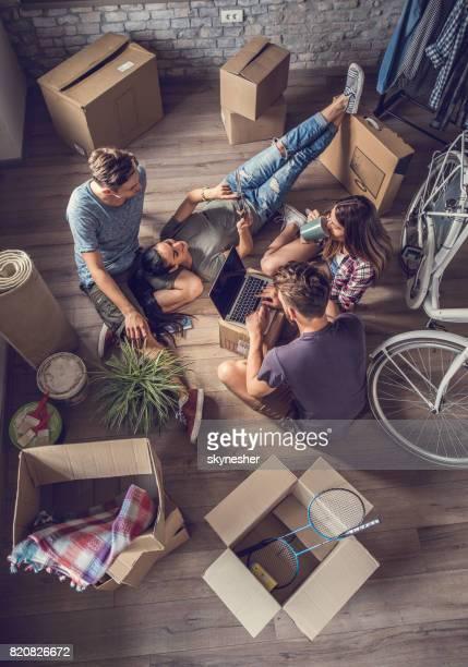 Avant avis des amis de détente et à l'aide de la technologie sans fil après avoir emménagé dans un nouvel appartement.