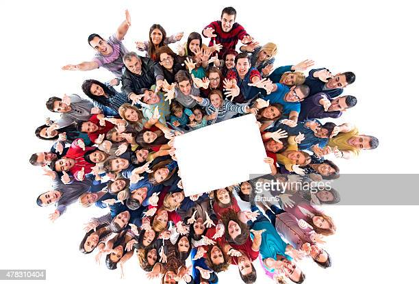 Above view of group of happy people holding white paper.