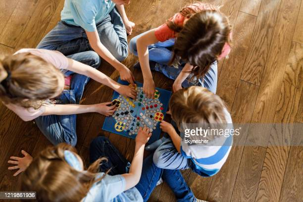 above view of group of kids playing ludo game on floor. - board game stock pictures, royalty-free photos & images