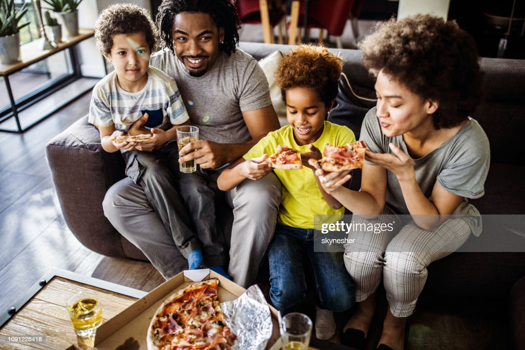 Above view of happy black family eating pizza at home. : Stock Photo