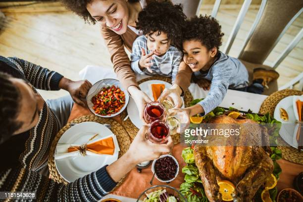 above view of happy black family toasting on thanksgiving day. - kids thanksgiving stock pictures, royalty-free photos & images