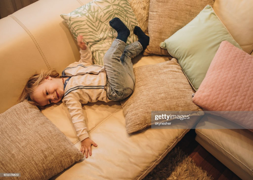 Above View Of Happy Boy Lying On Sofa In The Living Room Stock Photo