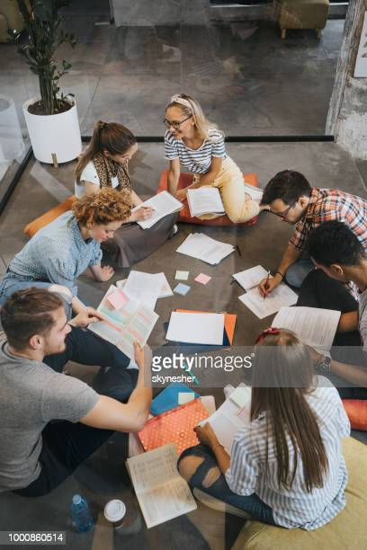 above view of happy college students studying on the floor at campus. - vertical stock pictures, royalty-free photos & images