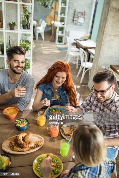 Above view of happy couples talking on a lunch in a restaurant.
