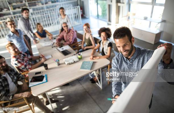 above view of happy entrepreneur explaining the business plan to his team on a presentation in the office. - equipamento à base de papel imagens e fotografias de stock