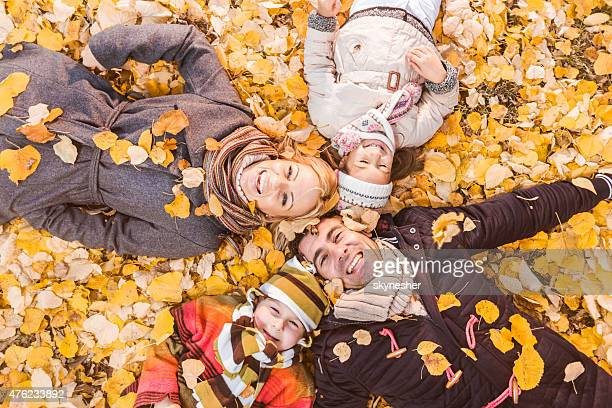 Above view of happy family lying in autumn leaves.