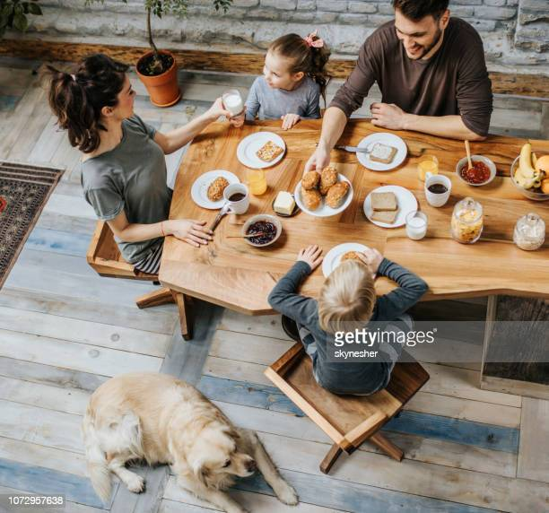 above view of happy family talking during breakfast at dining table. - dog eats out girl stock pictures, royalty-free photos & images