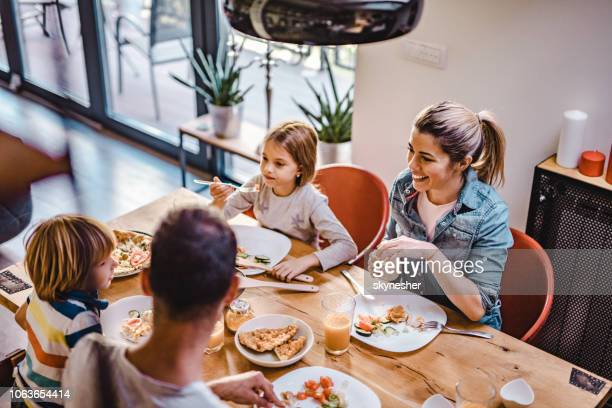 above view of happy family talking during lunch at dining table. - four people stock pictures, royalty-free photos & images